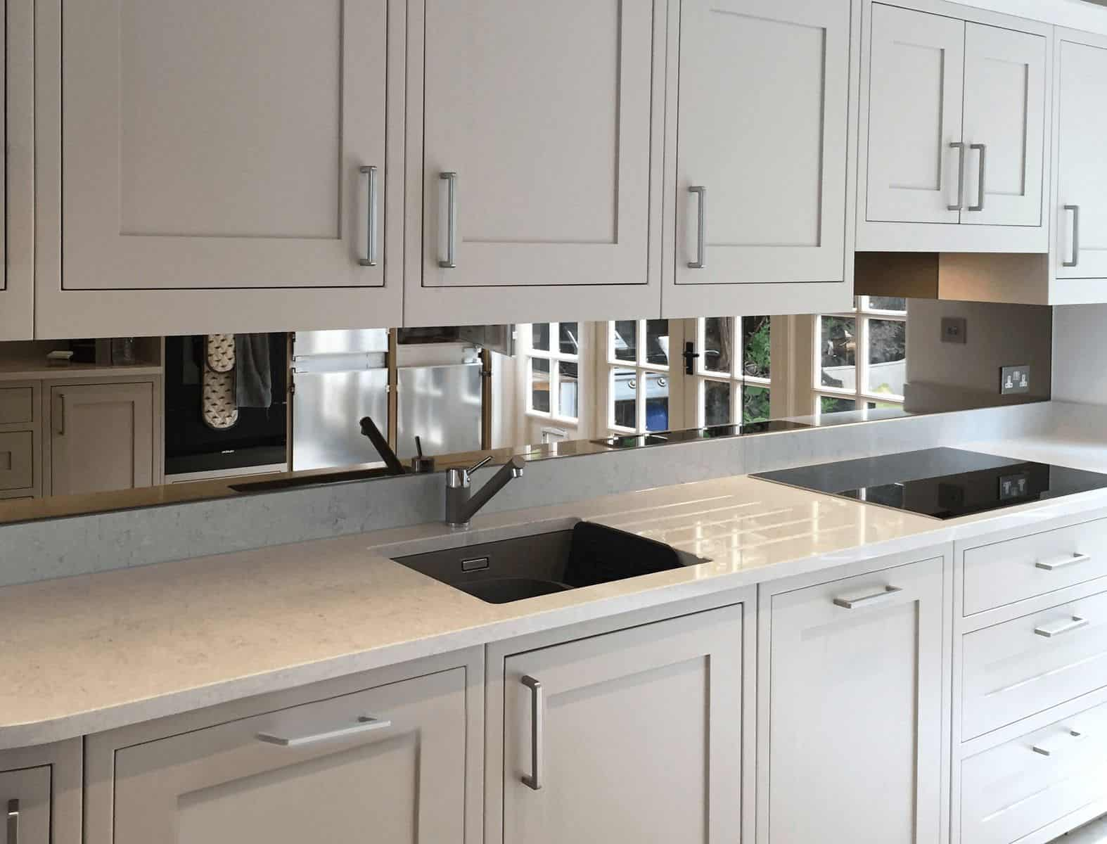Mirrored bronze tinted toughened glass splashback in a white Shaker style kitchen